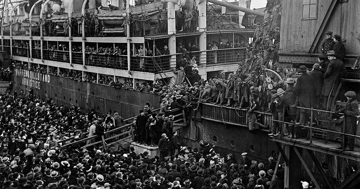 """""""Den 11/11 1918 var krigen afsluttet, og byen skiftede igen ansigt. Den blev en slags udvekslingssted for krigsfanger, som dukkede op i store maengder ivrigt jagtet af de såkaldte 'Langeliniepiger',"""" hedder det i en erindring. En stor folkemaengde følger her i Københavns Frihavn italienske soldater på vej hjem i 1919. Foto: Ukendt fotograf, Københavns Stadsarkiv"""