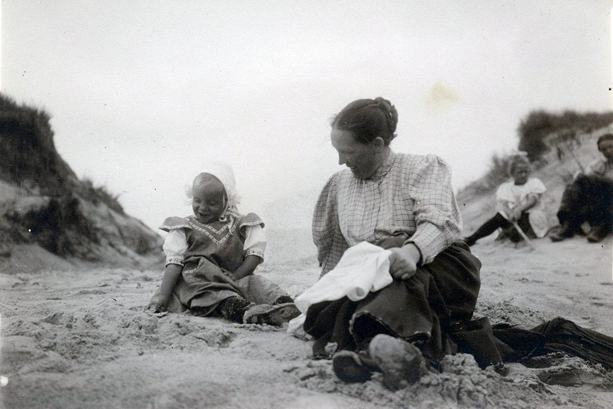 Ingrids mor sidder med den yngste søster på stranden. Foto fra Ingrid Agnete Muncks erindring, ukendt fotograf, Københavns Stadsarkiv