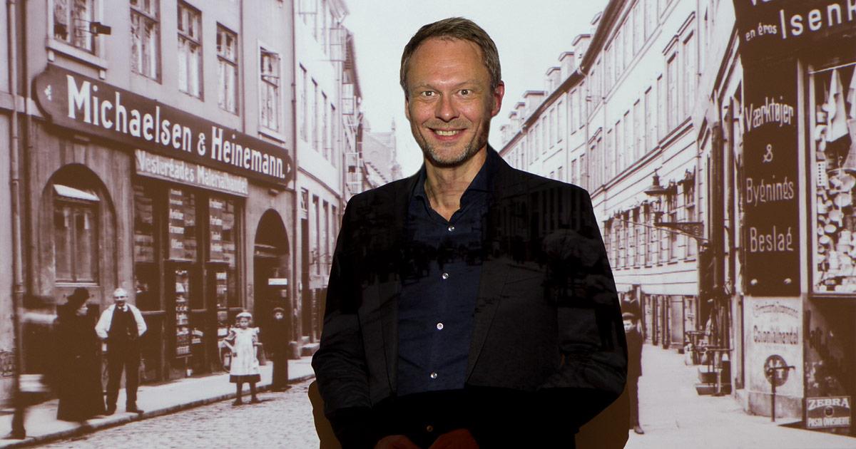 Carl Christian Ebbesen, kultur- og fritidsborgmester i Københavns Kommune, foran et fotografi af Vestergade, omkring år 1900. Foto: Ulrich Jacobsen