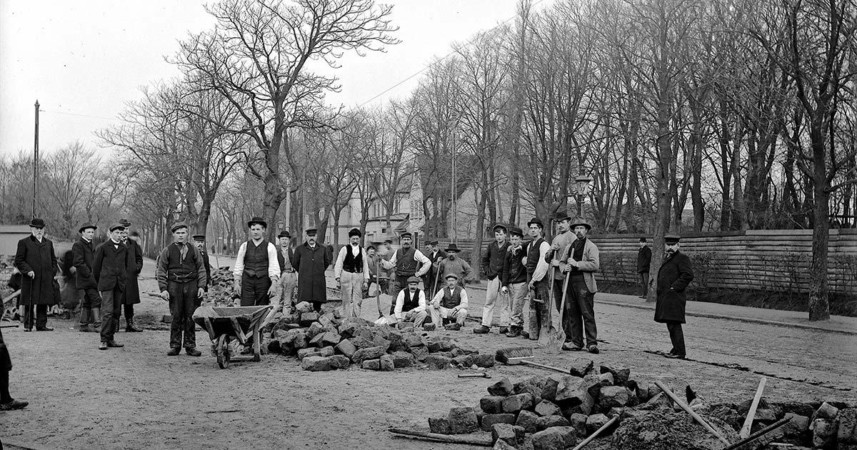 Forvalteren jagtede ikke idylliske motiver. I stedet fanger han blikket fra et par og tyve mænd, der d. 27. november 1907 lægger de brosten, der føjer Amagerbrogade sammen med Amager Boulevard. Foto: Ernst Nyrop Larsen.