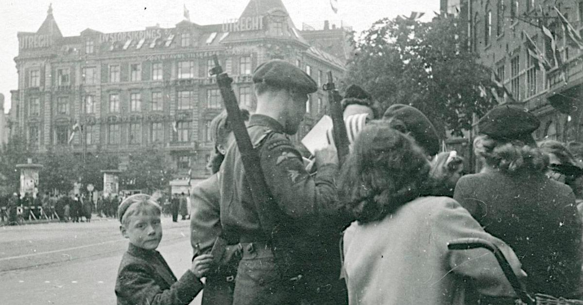 Engelske soldater skriver autografer på Rådhuspladsen, maj 1945. Drengen på billedet er ikke Ole Brage, men Ole fik sikret sig en autograf, da englænderne kom til Bryggen. Foto: Ukendt fotograf, Nationalmuseet