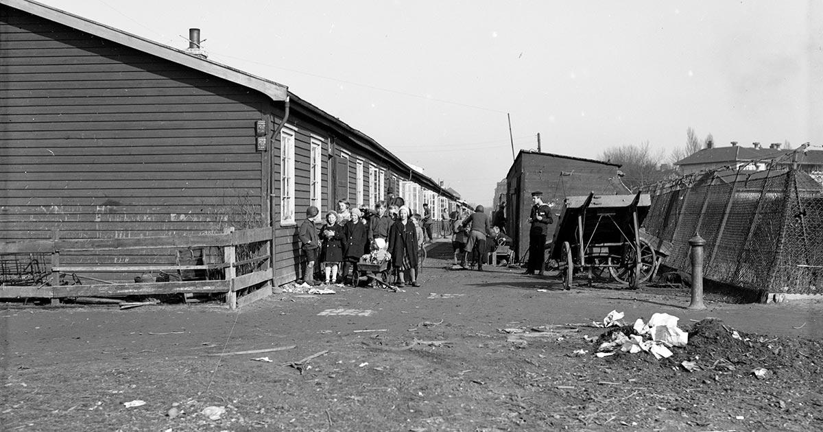 Da bolignøden i København nåede et kritisk niveau i 1916, blev det besluttet at bygge 'midlertidige' træbarakker til at huse mange af de husvilde børnefamilier. Billedet er fra den første barak-by, som var placeret mellem Sundholm og Sundbyvester Skole på Amager. Barakkerne blev brugt de næste 50 år. Foto: Ukendt fotograf, 1933, Københavns Museum.