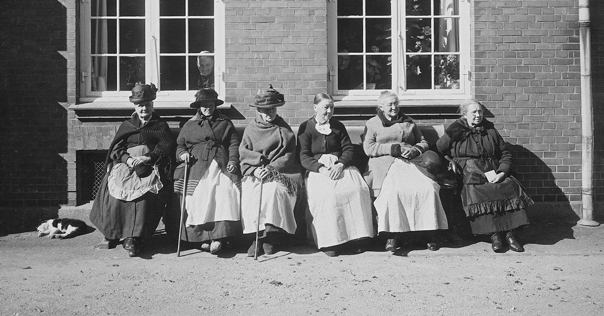 Ældre kvinder på en bænk i solen i De Gamles By, 1920'erne. Foto: Peter Elfelt, Københavns Stadsarkiv