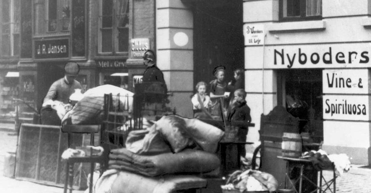 Den sociale nød under 1. verdenskrig resulterede i, at mange arbejderfamilier blev sat på gaden af kongens foged, der her holder vagt for at forhindre, at indboet slæbes op i lejligheden igen. Foto: Arbejdermuseet og Arbejderbevægelsens Bibliotek og Arkiv