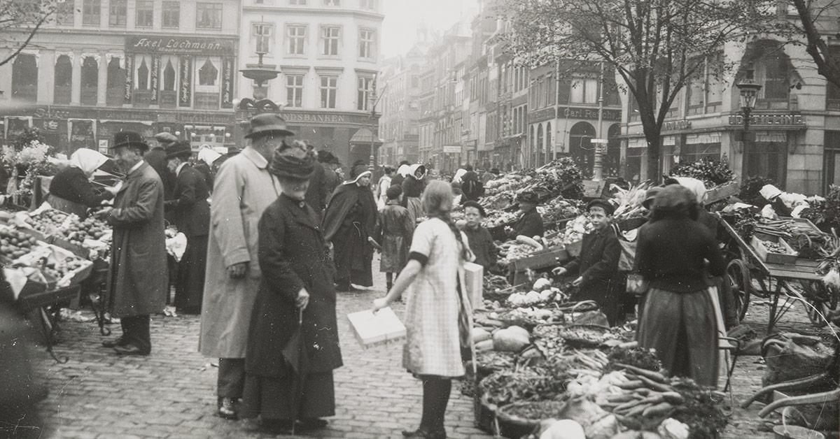 Udateret stemningsbillede fra Grøntorvet med mennesker og de udbudte varer i kurver og på vogne.