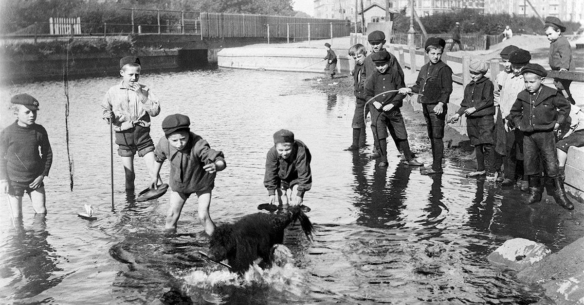 Gader, stræder og vandløb var legepladserne for byens børn. Her er det drenge, der leger i Ladegårdsåen med en hund. Ca. 1907. Foto: Fotograf ukendt, Københavns Museum