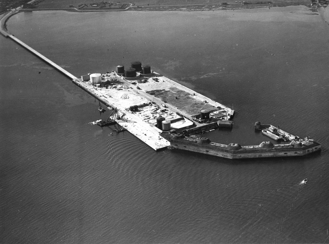 Prøvestenen, udateret, men ca. midten af 1930'erne. Havnevæsenet anlagde her en havn til olieprodukter i tilknytning til Prøvestensfortet. En dæmning skabte adgang til øen, men er senere erstattet af en ny. Øen er nemlig blevet udvidet kraftigt siden, og i dag håndteres også sten og grus. Foto: Københavns Stadsarkiv.