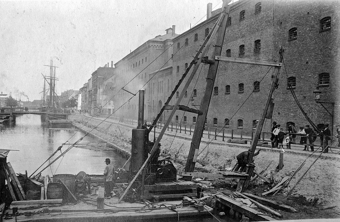 """Kanalen set mod nord fra Torvegade, udateret, men ca. 1900. Bygningen t.h. var Kvindefængslet, som i erindringerne om livet i København huskes som et skræmmende og uhyggeligt sted. Fængslet blev nedlagt og nedrevet i 1928 i forbindelse med en udvidelse af Torvegade. Københavnerne opfattede den nye hus fra 1930 som """"ultramoderne"""" og mærkelig og døbte det """"Lagkagehuset"""" efter de vandrette hvide og gule bånd – flødeskum og vanillecreme. Foto Københavns Stadsarkiv."""