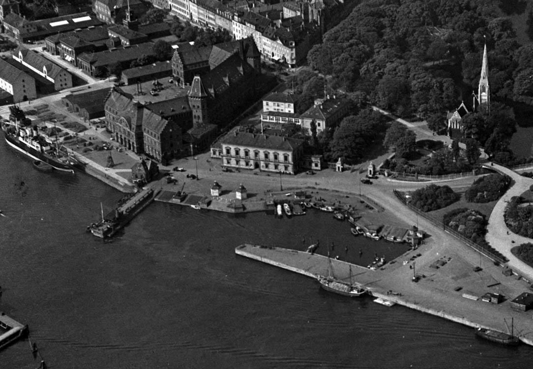 Ndr. og Sdr. Toldbod, ca. 1935. Havnevæsenets bygning er endnu ikke forhøjet med en ekstra etage. T.v. ses toldkammeret, hvor A.P. Møller - Mærsk i dag har hovedsæde. Området var toldområde og forbundet med Sdr. Frihavn i nord via Forbindelsesvej. Jernbanespor gik til Ndr. Toldbod og videre gennem Sdr. Toldbod til Larsens Plads. Jernbane og vej, der skar sig gennem Kastellet, er i dag fjernet i forbindelse med en reetablering af Kastellet. Foto: Københavns Stadsarkiv.