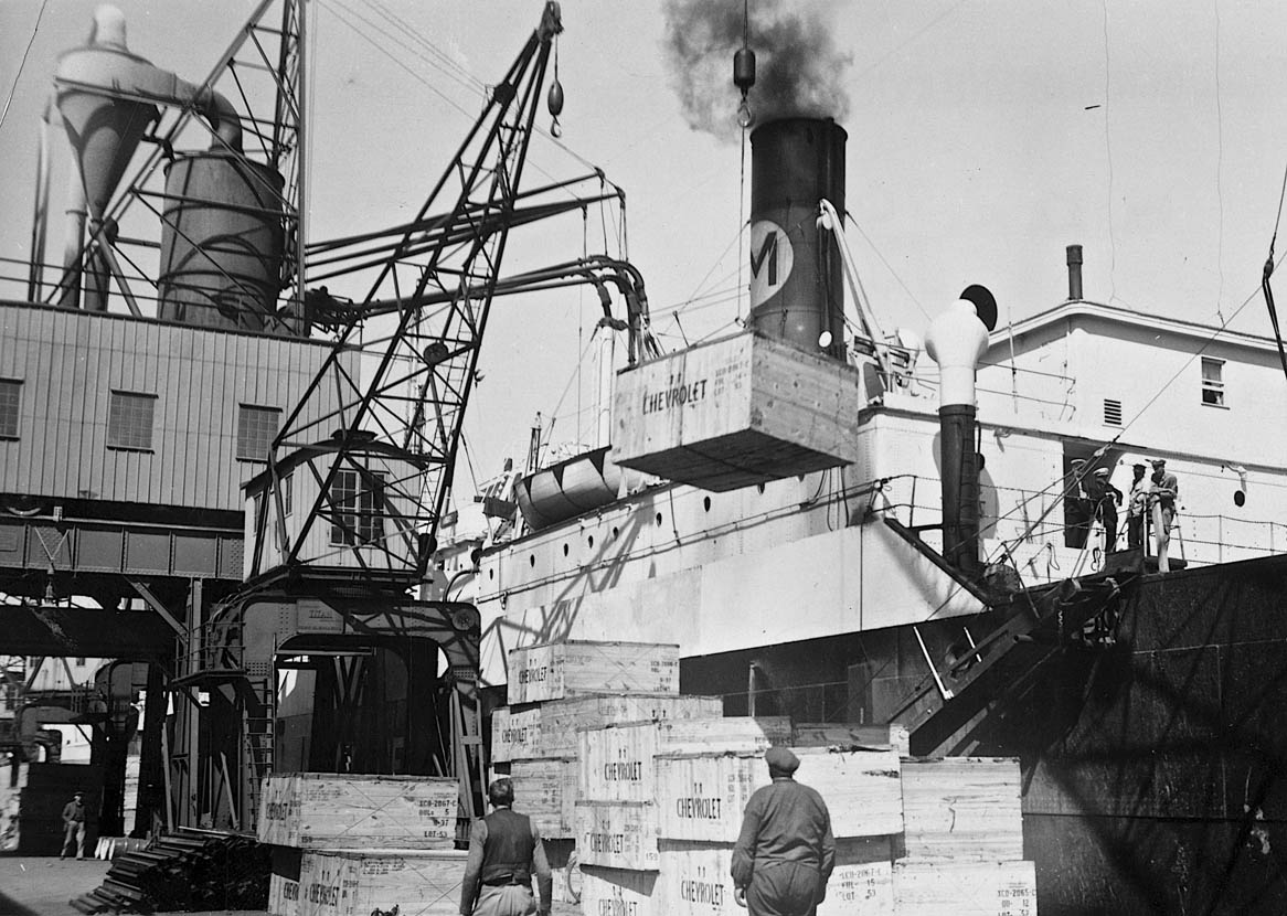 Vestkaj (Amerikakaj) i Sdr. Frihavn, udateret billede, men nok fra først i 1950'erne. Kasserne med bildele blev samlet færdigt hos General Motors. Bilkasser af træ var eftertragtede og en del endte som byggemateriale i københavnske kolonihaver. Skibet tilhørte det amerikanske rederi Moore-MacCormack Line, som i mange år sejlede fast på Frihavnen. Foto: Københavns Stadsarkiv.