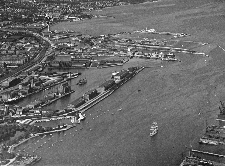 Havnen set mod nord, udateret, men ca. 1930. I forgrunden ses Langelinie og Sdr. Frihavn, som i dag rummer kontorer og boliger. Med få ændringer så Sdr. Frihavn sådan ud til 1990'ernes byudvikling. I 1950'erne blev der opført en passagerterminal på Vestkajen (Amerikakaj), fortrinsvis til betjening af Amerikabådene. Det store silopakhus på Midtermolen brændte i 1968. Foto: Københavns Stadsarkiv