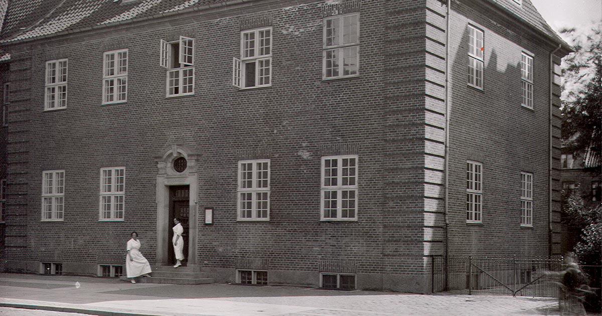 Foran indgangen til badet i Sjællandsgade står de ansatte kvinder klædt i hvide kitler. 1922 Foto: Fotograf ukendt, Københavns Stadsarkiv