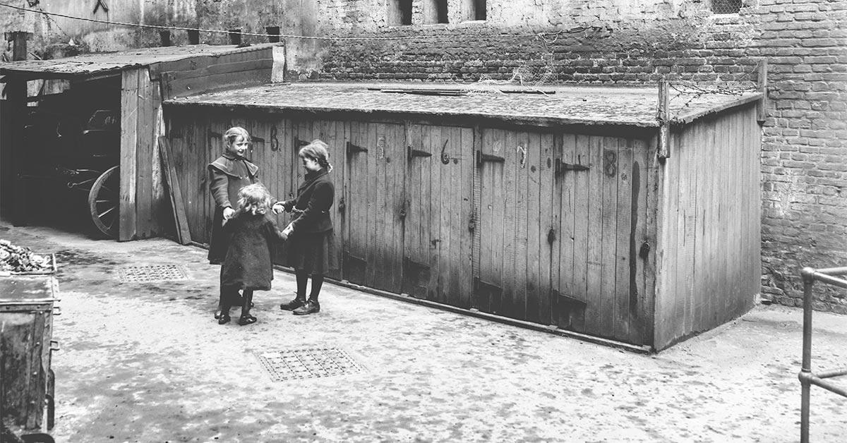 Leg i byens baggårde krævede fantasi i en tid uden sandkasser og gyngestativer. Her er børn i gården i Fredericia fælles om noget, der kunne være en sangleg. Foto: Fotograf ukendt, Københavns Museum