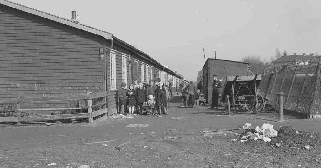 Da bolignøden i København nåede et kritisk niveau i 1916, blev det besluttet at bygge 'midlertidige' træbarakker til at huse mange af de husvilde børnefamilier. Billedet er fra den første barak-by, som var placeret mellem Sundholm og Sundbyvester Skole på Amager. Barakkerne blev brugt de næste 50 år. Årstal: Cirka 1933. Københavns Museum.