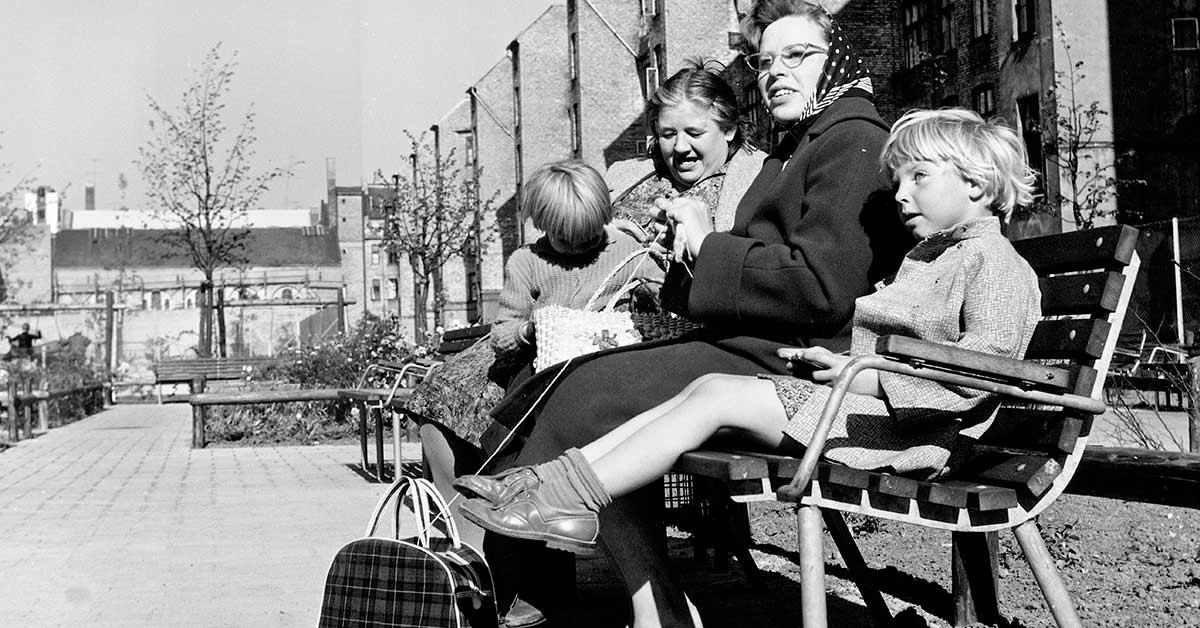 Kvinder med børn i anlæg. Efter sanering på Vesterbro var erstattet af rekreativt gårdmiljø. Det er Apostelkirkens bygning der anes bag muren i baggrunden. 1961. Foto: Fotograf ukendt, Københavns Stadsarkiv
