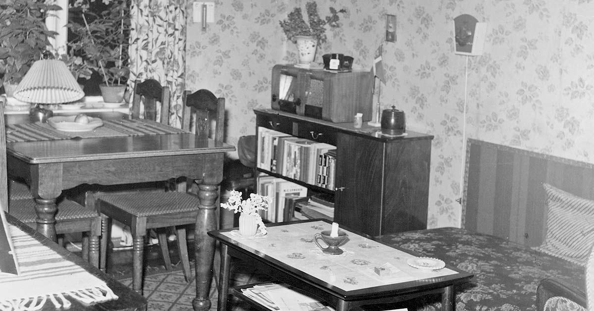 Familien, der boede i den lille toværelses lejlighed i forhuset, brugte værelset mod gaden som spise- og dagligstue. Formodentlig blev det også brugt som soveværelse for en eller flere af familiens medlemmer. 1953. Foto: Fotograf ukendt, Københavns Stadsarkiv