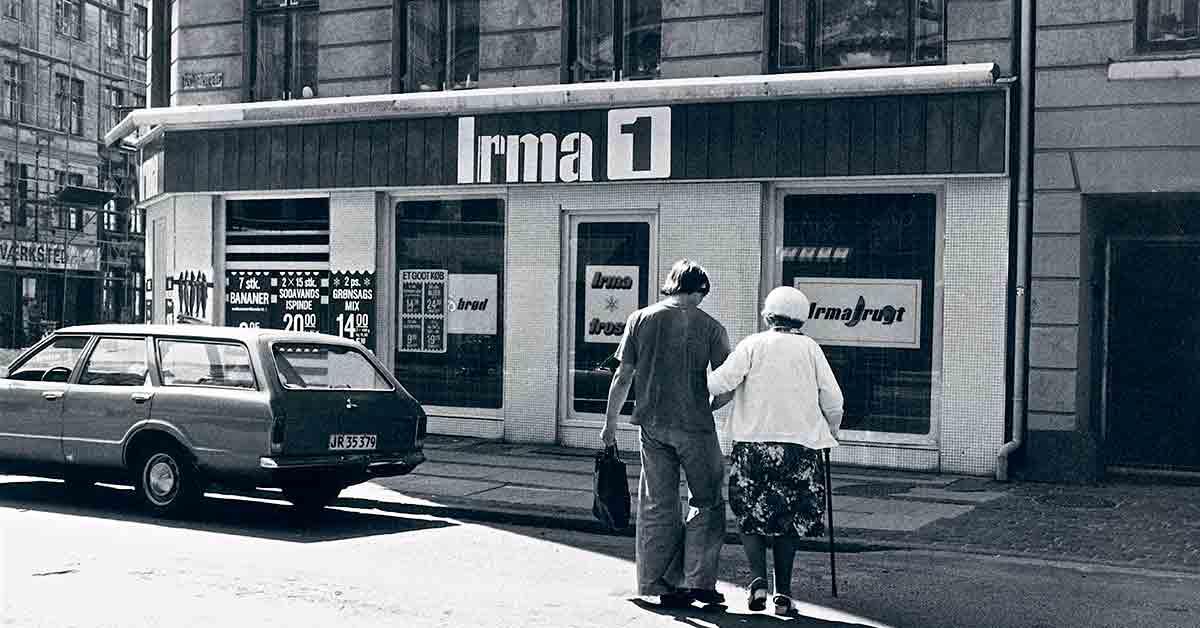 Hjemmehjælper går med borger over Dybbølsgade foran en Irma. År: 1982. Foto: Fotograf ukendt, Københavns Museum.