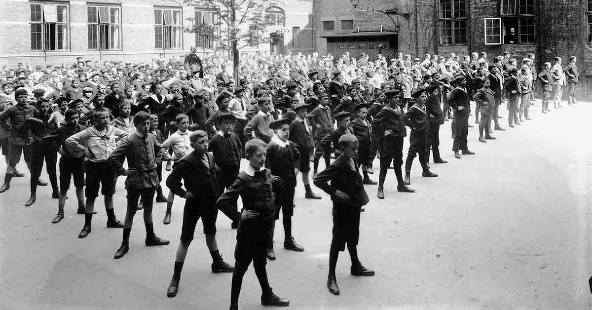 Skoleelever motionerer i skolegården på Efterslægtens Skole. År: 1911. Foto: Fotograf ukendt, Københavns Museum.