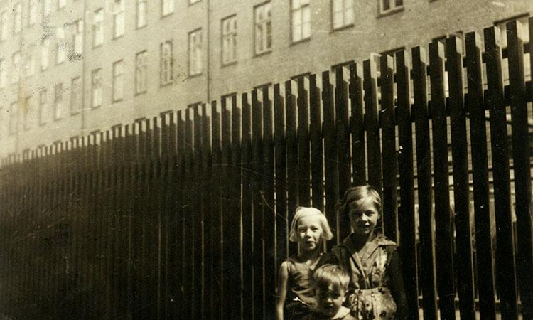 Tre børn stående foran et plankeværk i gården ved Vesterfælledvej, 1933. Foto fra erindring af Grete Andersen, født 1925. Ukendt fotograf. Københavns Stadsarkiv