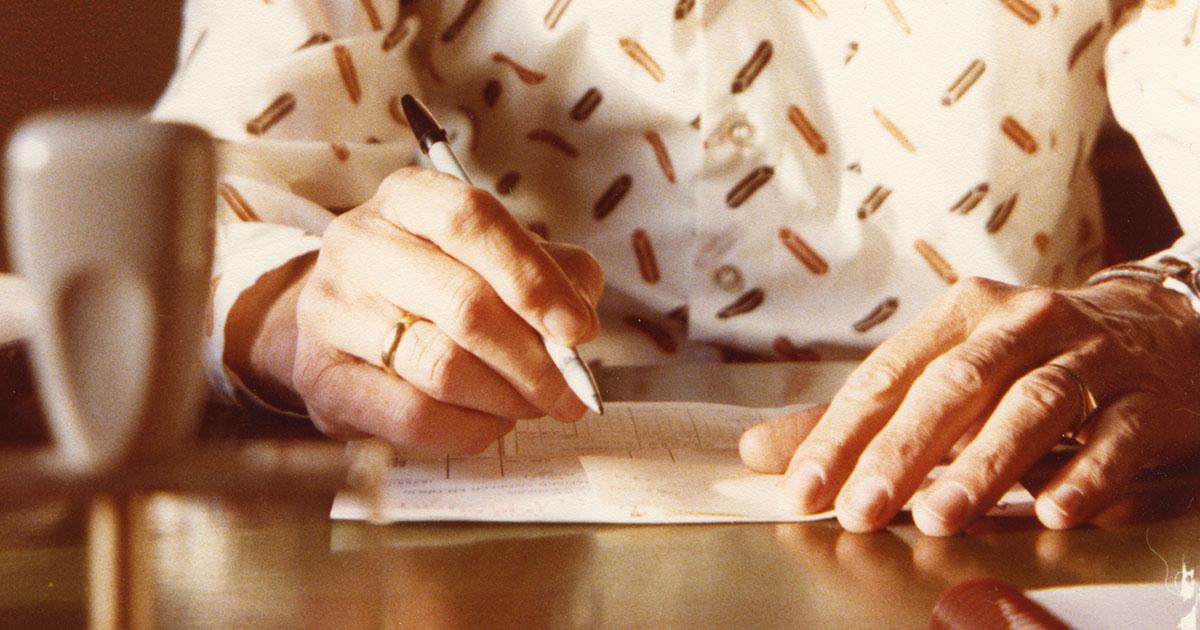 Person, der skriver. Fokus på hænder og kuglepen