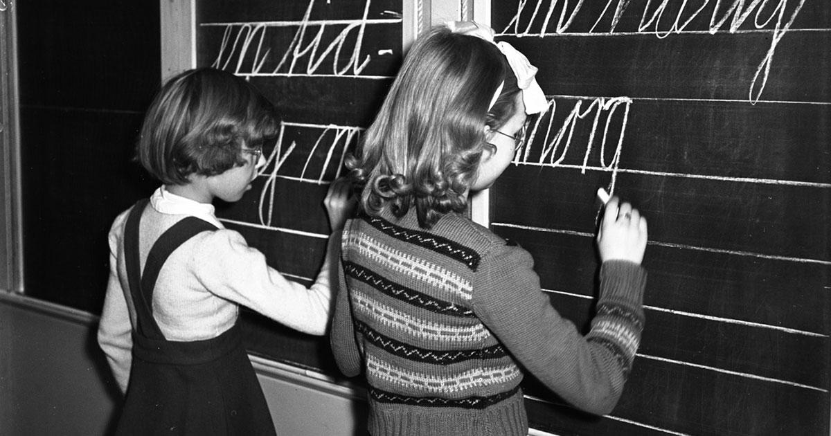 Skolepiger skriver på tavle